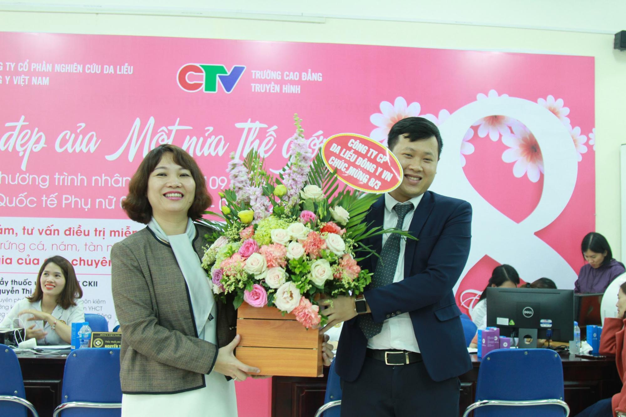 Ông Nguyễn Thành Long tặng hoa cho bà Nguyễn Thanh Liêm - Chủ tịch công đoàn trường Cao đẳng truyền hình